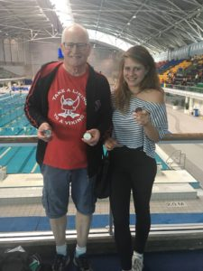 John Collis proudly displaying his medals with daughter Georgie.