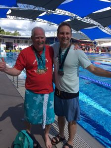 Image shows John and Adam poolside with their medals