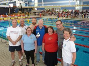 This image shows Molonglo Water Dragons team members poolside. Left to right: Ross Burden, Gary Stutsel, Mary Liz Partridge, Gavin Atherton, John Collis, Tanya Colyer, Ed Auzins and Margaret Larkin