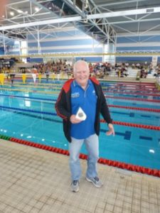 This image shows Water Dragons President John Collis with the trophy for first place in the 3rd Division at the NSW Short Course Championships